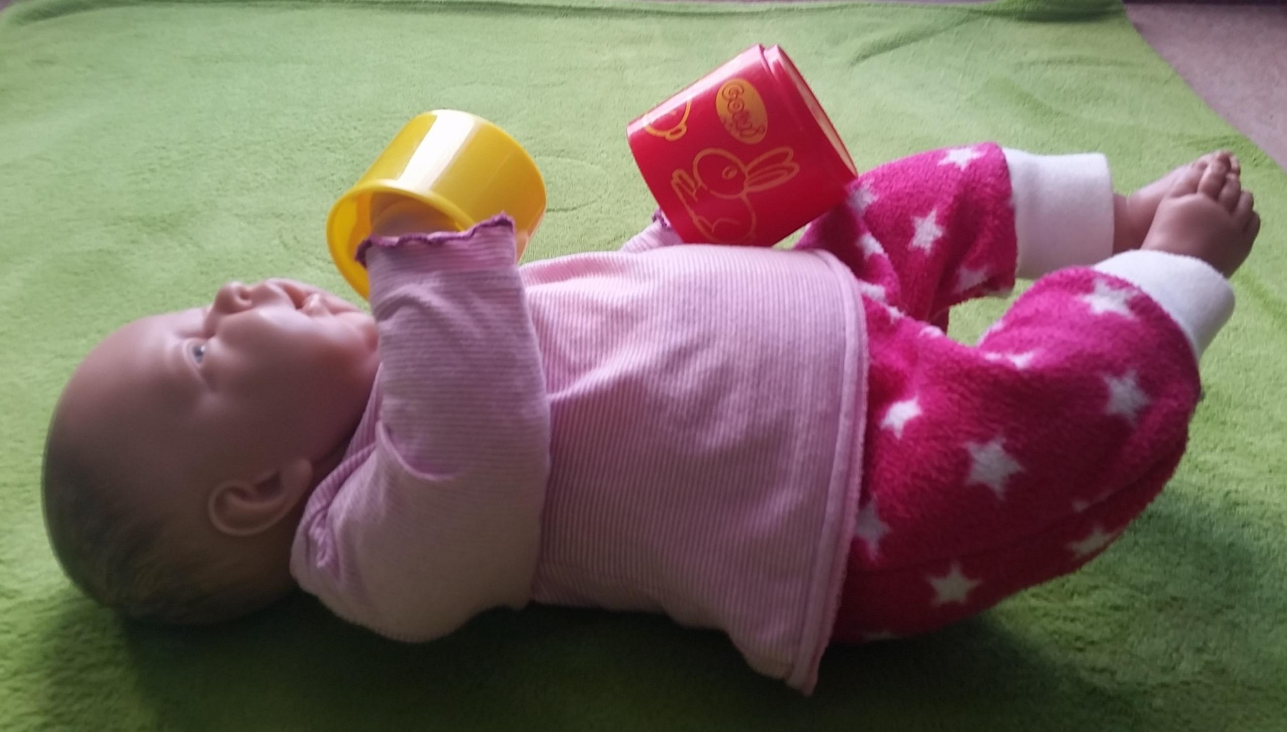Das Kind hält 2 Becher mit den Händen.